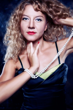 portrait of a young, beautiful curly blonde girl with beautiful red nail polish, red lipstick and pearl necklace