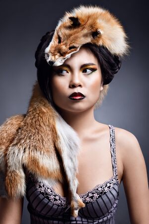 portrait of a beautiful girl with extravagant makeup and skin red fox on her head