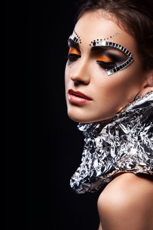 portrait of a beautiful girl with a futuristic make-up with a metal neck braces