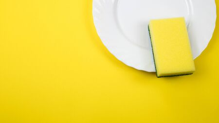 Photo for Cleaning sponge on a white plate on a yellow background. - Royalty Free Image