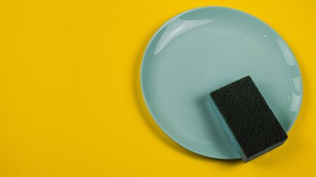 Photo for Cleaning sponge on a green plate on an orange background. - Royalty Free Image