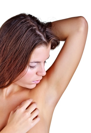 Photo pour Beautiful girl looks armpit, isolated on white background - image libre de droit