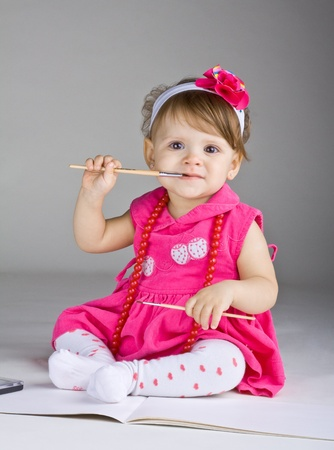 Photo for Seated little girl holding a paintbrush, on a dark background - Royalty Free Image