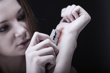 Young woman cuts veins on a hand on a dark background. Focus on hand