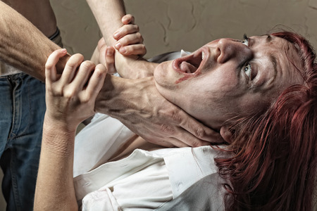 Victim of domestic violence. Husband strangles his wife, she cries
