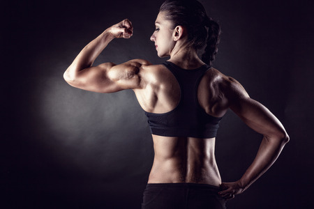 Foto de Athletic young woman showing muscles of the back and hands on a black background - Imagen libre de derechos