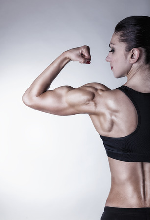 Athletic young woman showing muscles of the back and handson on a gray background