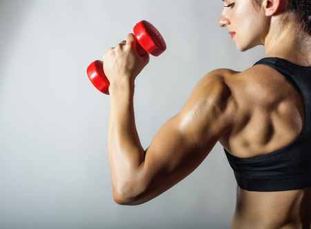 Foto de Fitness woman with barbells on grey background - Imagen libre de derechos
