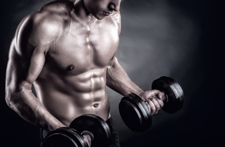 Foto de Closeup of a muscular young man lifting weights on dark background - Imagen libre de derechos