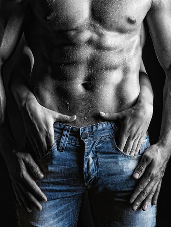 Photo pour Sexy muscular man and female hands unbuckle his jeans on a dark  - image libre de droit