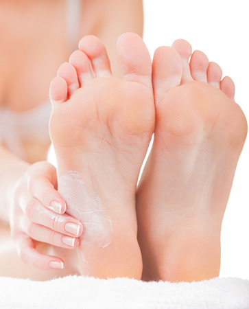 Close-up woman applying moisturizer cosmetic cream on foot on light background