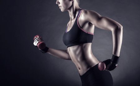 Foto de Fitness girl with dumbbells on a dark background - Imagen libre de derechos
