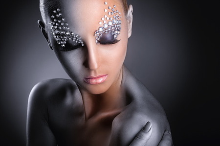 Foto de Close-up of young woman with fashion makeup with rhinestone on a dark background - Imagen libre de derechos