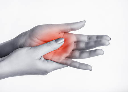 A woman massaging her painful hand isolated on a white background