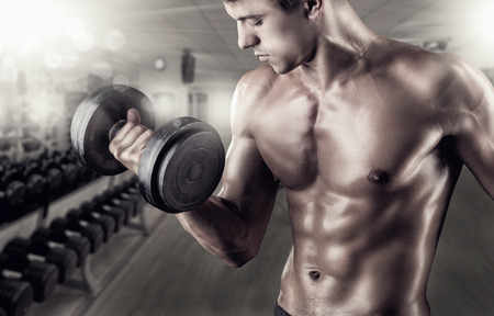 Foto de Close Up of a muscular young man lifting weights in the gym - Imagen libre de derechos