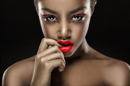 Foto de Close-up of a beautiful black woman with fashion make-up, red lips. Glamorous portrait - Imagen libre de derechos