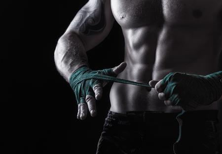 Foto de Close up of a boxer putting on straps preparing for combat on a dark background - Imagen libre de derechos