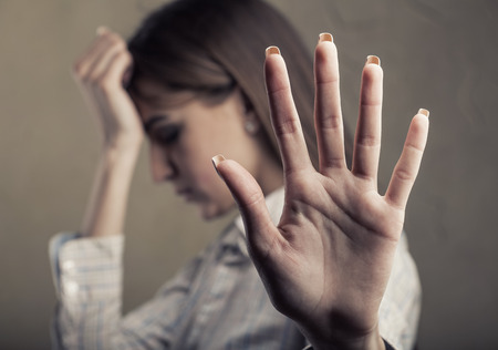 Young tired woman shows a hand sign stop. Focus on the hand