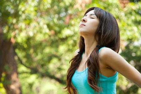 Young woman taking a deep breath, enjoying fresh air in green park