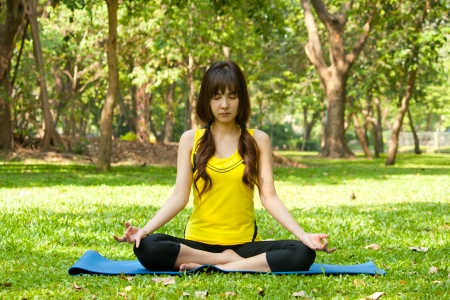 Beautiful young asian woman doing yoga on green grass at park