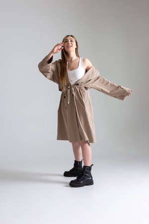 Photo pour attractive caucasian skinny girl in raincoat posing on white studio cyclorama - image libre de droit