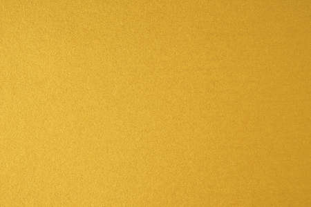 Glittering gold paper sheet texture background. Sparkling golden yellow pattern.