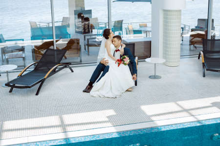 Wedding couple in love. Beautiful bride in white dress and veil and brides bouquet with handsome groom in blue suite sitting on plank bed and embracing each other indoors at pool. Full lenght portrait of man and girl. Concept of wedding celebration in vac