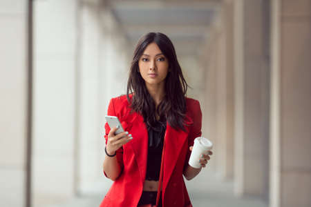 Foto de Young Asian woman with smartphone standing against street blurred building background and looking. Fashion business photo of beautiful girl in red casual suite with phone and cup of coffee - Imagen libre de derechos