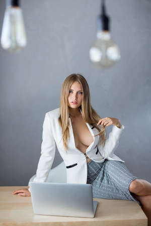 Bulbs. Sexy business woman or secretary with notebook computer pc wearing white suit with decollete big breast sitting on tabler against copy space gray wall background web camera chating surfing internet looking at camera.