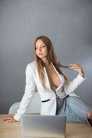 Sexy business woman or secretary with notebook computer pc wearing white suit with decollete big breast sitting on tabler against copy space gray wall background web camera chating surfing internet in seduction pose.