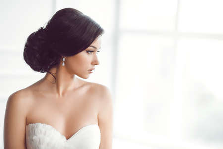 Foto de Beauty portrait of bride wearing fashion wedding dress with feathers with luxury delight make-up and hairstyle, studio indoor photo. Young attractive multi-racial Asian Caucasian model. Profile of sensual beautiful young woman like a bride in white room a - Imagen libre de derechos