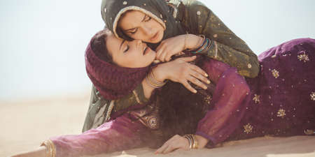 Desert women thirsty dehydrated lying on sand outdoors. Dehydration, overheating, thirst and heat stroke concept image with two sisters in desert nature.Portrait of two beautiful mixed race asian caucasianl arabian girls lost in desert during journey.