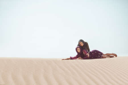 Desert women thirsty dehydrated lying on sand outdoors. Dehydration, overheating, thirst and heat stroke concept image with two sisters in desert nature. Two beautiful mixed race asian caucasianl arabian girls lost in desert during journey.