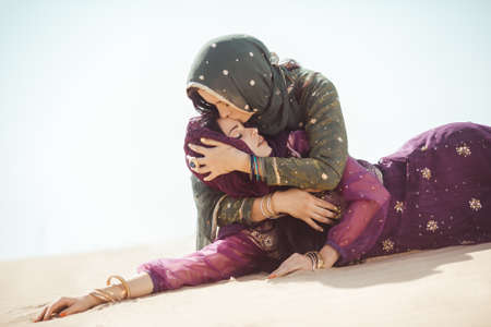 Desert women thirsty dehydrated lying on sand outdoors. Dehydration, overheating, thirst and heat stroke concept image with two sisters in desert nature.Portrait of two beautiful mixed race asian caucasian arabian girls lost in desert during journey.
