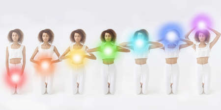 Woman meditating. Colored chakra lights over her body. Yoga, zen, Buddhism, recovery and wellbeing concept.