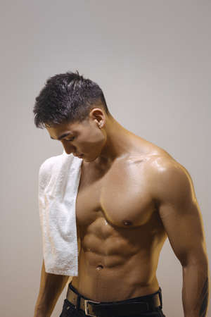 Photo for Portrait of Asian male athlete after workout against a gray background. Side view of young man shirtless looking exhausted after the gym. Handsome muscular man after sports training with a white towel. - Royalty Free Image