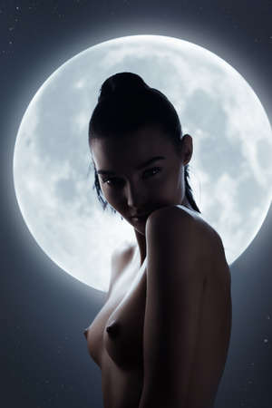 Photo for Fine art fashion studio silhouette portrait of a nude sensual woman against the night sky and a full moon. Stunning face, perfect body, slim figure, beautiful breast. Young adult mixed race Asian Caucasian model seductive look. Art of erotica - Royalty Free Image