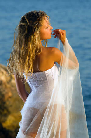 beautiful bride stands at the sea