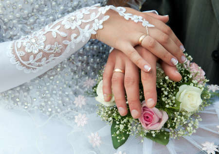 Foto de Hands of groom and bride with wedding rings on top of the brides bouquet - Imagen libre de derechos