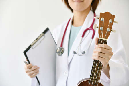 Photo for Doctor hand holding ukulele (musical instrument), Music therapy concept. (Selective Focus) - Royalty Free Image