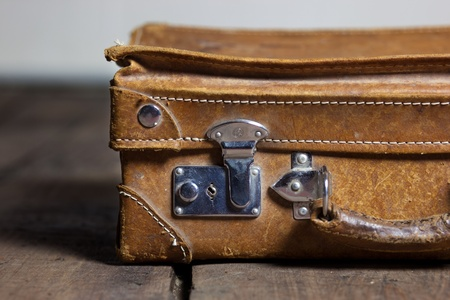 old shabby leather portable suitcase for travel trip on floor