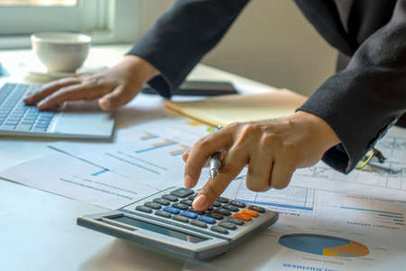 Foto de Male accountants are working on financial documents and calculators for business and finance expenses. - Imagen libre de derechos