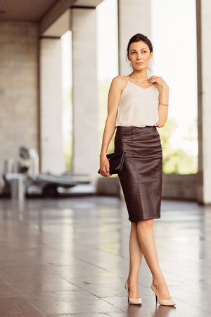 Portrait of a business woman in leather skirt with