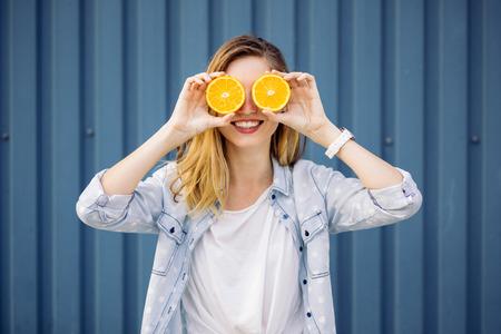 Foto für Smiling woman holding two grapefruits in hands on a blue background - Lizenzfreies Bild