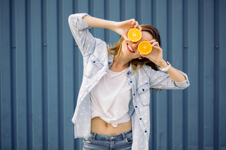 Foto de Smiling woman holding two grapefruits in hands on a blue background - Imagen libre de derechos