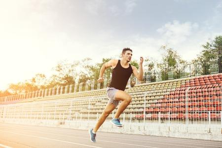 Foto de Athletic man running on a racing track - Imagen libre de derechos