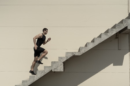 Foto de Up to top, overcoming challenges. Strong athletic man climbing stairs - Imagen libre de derechos