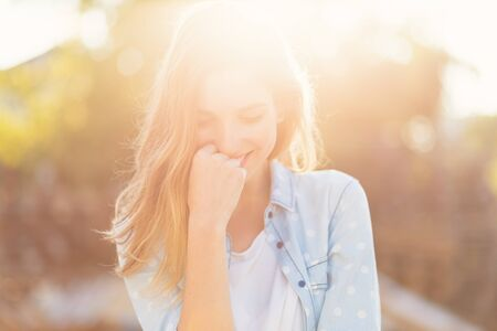 Foto de Portrait gorgeous girl with a beautiful smile and attractive facial features on a sunny day with rays reflected on her face. Romantic, fresh, atmospheric people concept. - Imagen libre de derechos