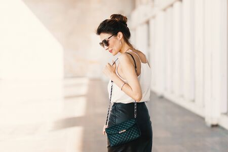 Photo for Beautiful smiling young woman in sunglasses wearing leather clutch and skirt, white easy blouse and looking away over the shoulder while walking outdoors. Spirit of the city. - Royalty Free Image