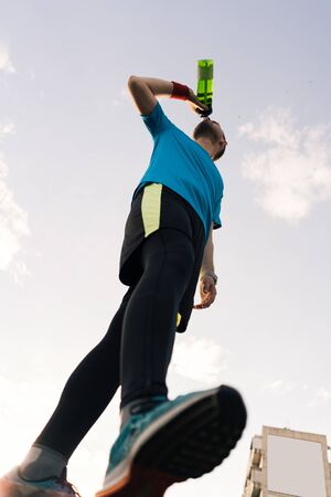Photo pour Low angle view of a sportsman drinking water with sky in background - image libre de droit